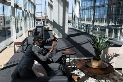 Young businessman sitting on the sofa and using virtual reality headset in office