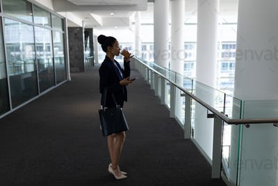 Pretty young businesswoman having coffee while using mobile phone in modern office