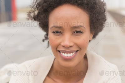 Portrait of happy young African American woman looking at camera. She is smiling
