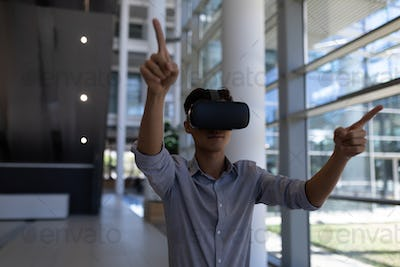 Front view of young Asian male executive using virtual reality headset standing in modern office