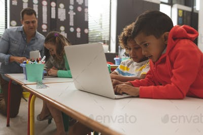 Two school boys working and scrolling on one laptop