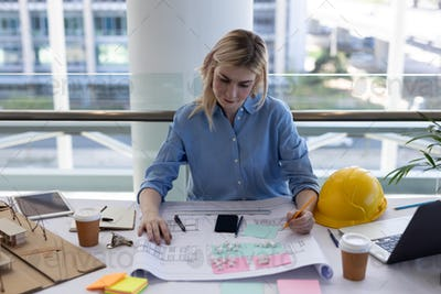 Front view of blonde young Caucasian female architect working at desk in modern office