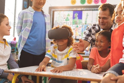 Front view of a schoolboy using virtual reality headset with his classmate and teacher at school