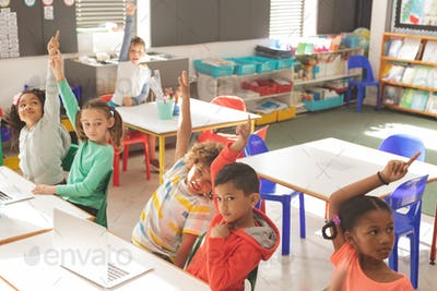 Overhead view of school kids raising hand to answer of teacher question in classroom at school
