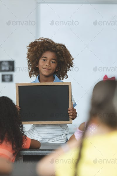 Front view of an Arican ethnicity schoolboy holding a slate and looking at camera in classroom