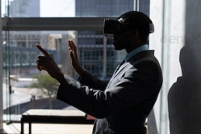 Young African-American businessman using virtual reality headset standing in modern office
