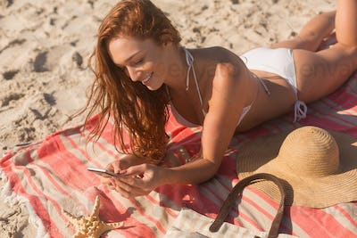 Gorgeous young Caucasian woman in bikini lying on sand and using her mobile phone on the beach.
