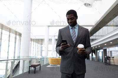Young African-American businessman with coffee cup using mobile phone standing in modern office.