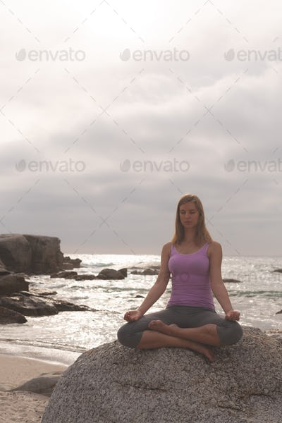 Front view of Caucasian blonde woman perform yoga on the beach. She is relaxed