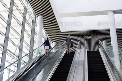 Low angle view of young multi-ethnic businesswomen using escalator in modern office