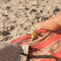 Low section of beautiful Caucasian woman tanning lying on the beach. It is sunny day