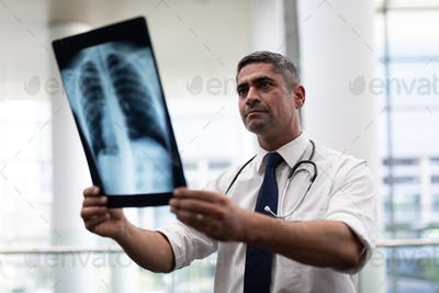 Front view of attentive mature Caucasian male doctor looking at x-ray standing in clinic