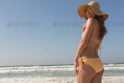 Beautiful young Caucasian woman in bikini and hat looking at camera standing on the beach.