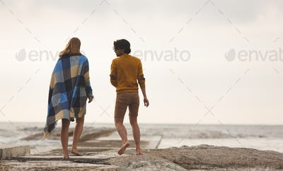 Rear view of young Caucasian couple walking on rock near beach