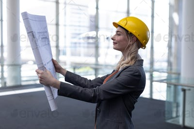 Smiling young blonde Caucasian female architect looking at blueprint in modern office.