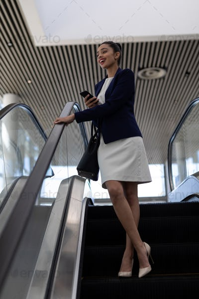 Happy young mixed-race businesswoman with mobile phone using escalator in modern office.