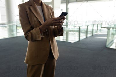 Mixed-race businesswoman using mobile phone in office lobby against view on street in background