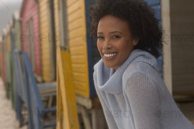 Happy young African American woman standing at beach hut.