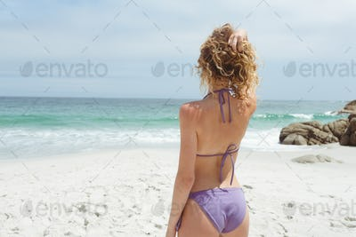 Rear view of caucasian woman standing with hand on hair and looking at seaon beach