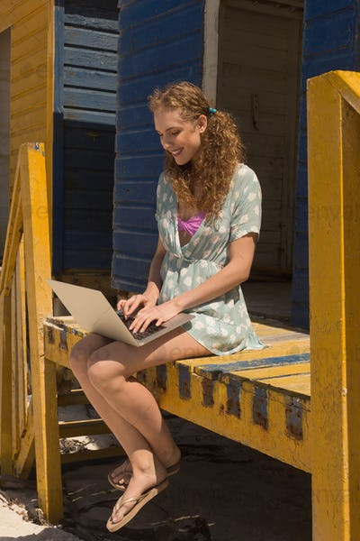 Side view of happy gorgeous young Caucasian woman using laptop sitting on beach hut. She is smiling