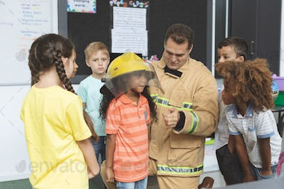 Caucasian firefighter interacting with school kids while one of them holding fire helmet on her head