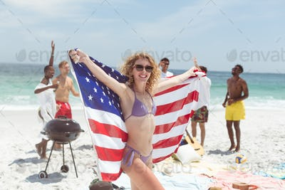Caucasian woman standing and holding american flag while her diverse friends having fun behind her