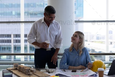 Happy Caucasians architects interacting with each other at desk in modern office.