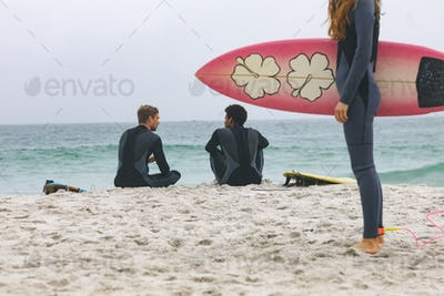 Diverse male friends interacting with each other while woman standing with surfboard on beach