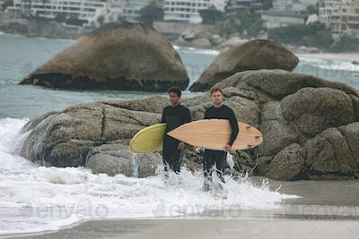 Front view of young multi-ethnic male friends standing on beach while holding surfboards