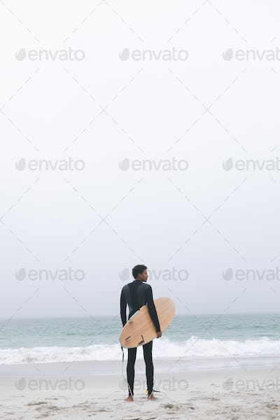 Thoughtful young mixed-race male surfer holding surfboard on the beach.