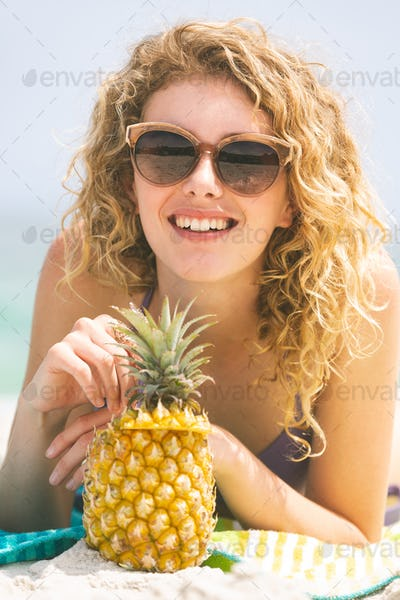 Close up of Caucasian woman lying at beach while having pineapple