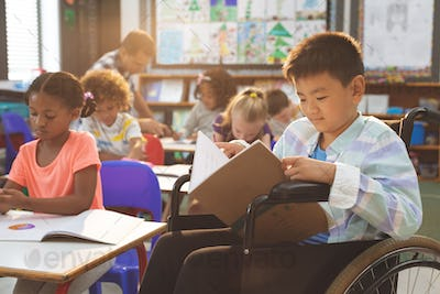 Side view of schoolboy studying in classroom while sitting at wheelchair in clasroom at school