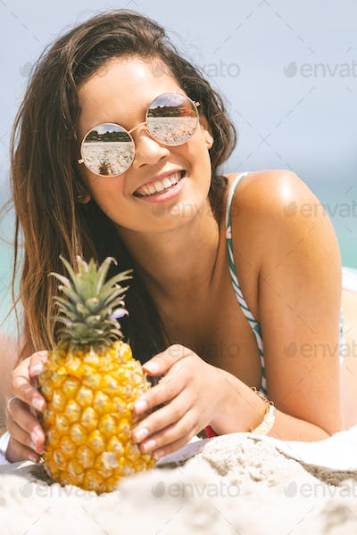 front view of caucasian woman lying at beach while having pineapple on sunny day