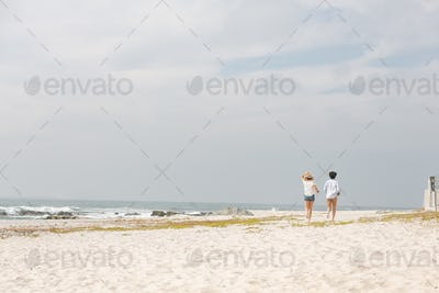 Rear view of happy young Caucasian couple running at beach on a sunny day