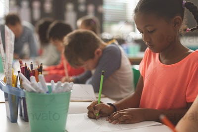 Mixed-race school girl writting on his notebook in a classroom
