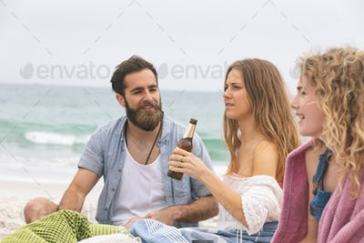 Front view of multi ethinc group of friends enjoying and interacting on beach while having beer