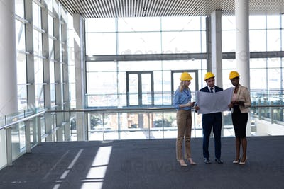 Front view of multi-ethnic architects discussing over blueprint in modern office