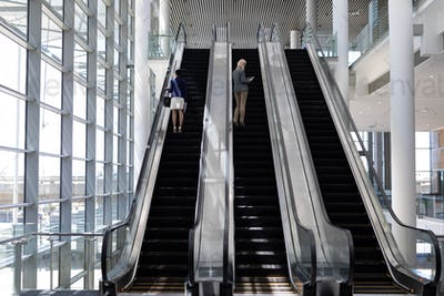 Rear view of young multi-ethnic businesswomen using escalator in modern office