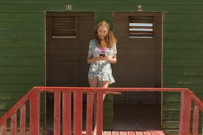 Front view of happy gorgeous young Caucasian woman using mobile phone at beach hut. She is smiling