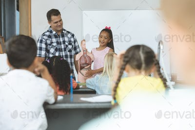 Schoolgirl explaining to his classmates the functioning of body human thanks to a dummy skeleton