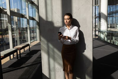 Businesswoman leaning against wall and using mobile phone in modern office