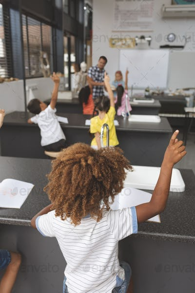 Rear view of school kids raising hand in classroom at school with teacher in background