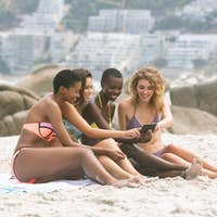Side view of multi ethnic women reviving photos on beach while holding mobile phone