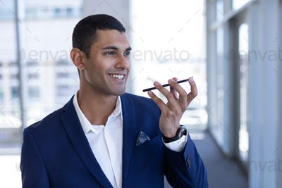 Happy young mixed-race businessman talking on mobile phone standing in modern office.
