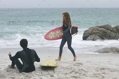 Rear view of young multi-ethnic couple interacting with each other on beach with surfboards