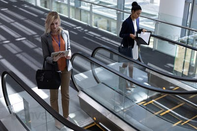 Front view of young multi-ethnic businesswomen using escalator in modern office