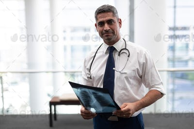 Male doctor with x-ray looking at camera standing in clinic