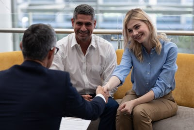 Caucasians business executives shaking hand while sitting on the sofa in modern office