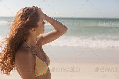 Woman in bikini caressing her hair on the beach