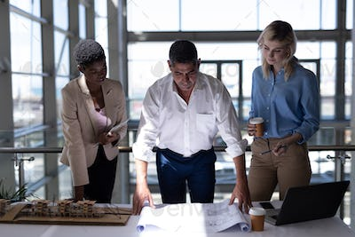 Front view of multi-ethnic architects working at desk in modern office. The are working hard